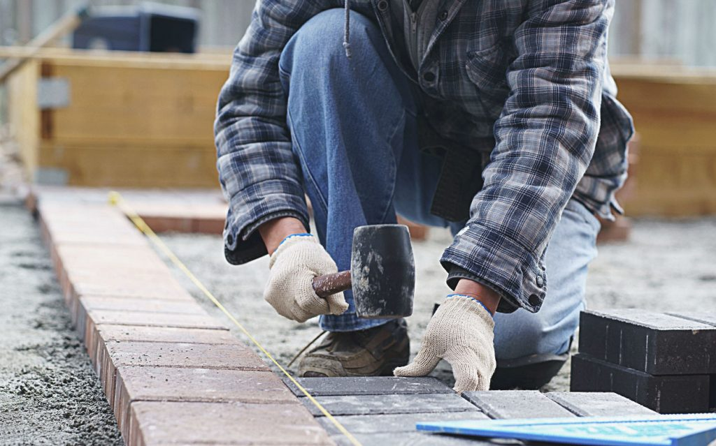 Driveway contractor installs stone pavers for a new driveway